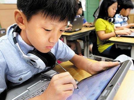 школьник прилежно тычет в экран компьютера пером